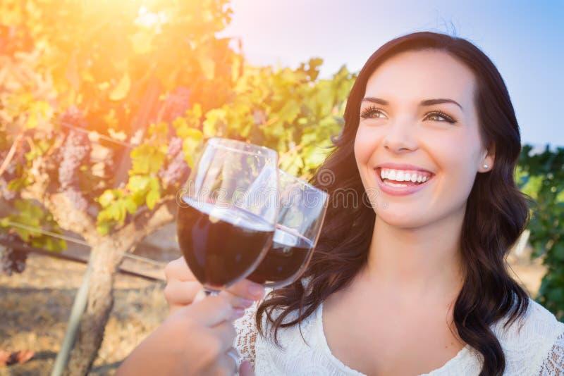 Bella giovane donna adulta che gode del bicchiere di vino che assaggia pane tostato nella vigna con gli amici fotografia stock libera da diritti