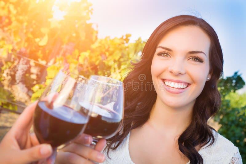 Bella giovane donna adulta che gode del bicchiere di vino che assaggia pane tostato nella vigna con gli amici immagini stock