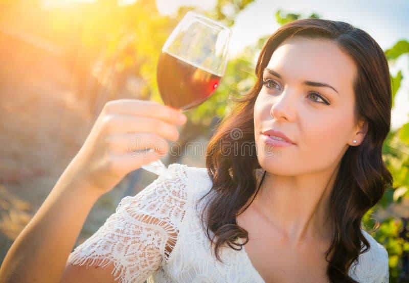 Bella giovane donna adulta che gode dell'assaggio del bicchiere di vino nella vigna immagini stock