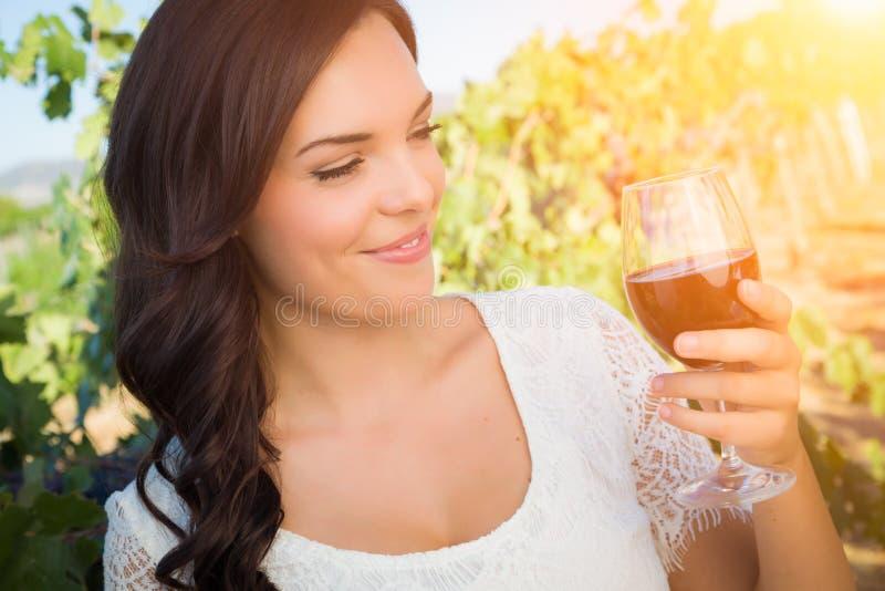 Bella giovane donna adulta che gode dell'assaggio del bicchiere di vino nella vigna fotografia stock libera da diritti