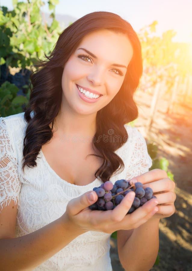 Bella giovane donna adulta che gode di una passeggiata in una vigna dell'uva fotografie stock libere da diritti
