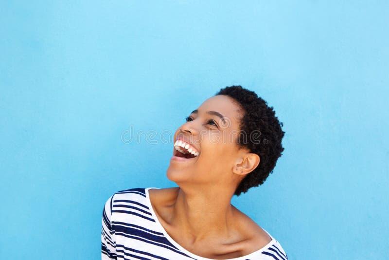 Bella giovane donna africana che ride contro il fondo blu fotografia stock