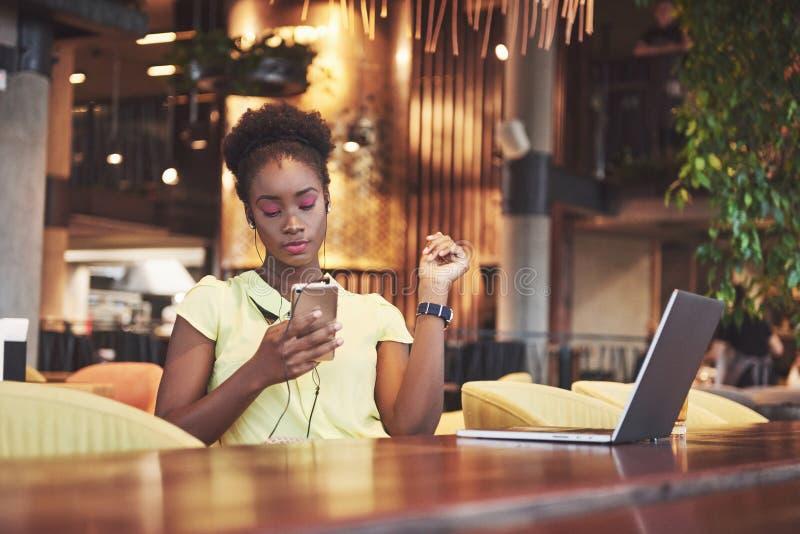 Bella giovane donna afroamericana di affari che aspetta il suo amico in un caffè, in un telefono ed in un computer portatile fotografie stock libere da diritti