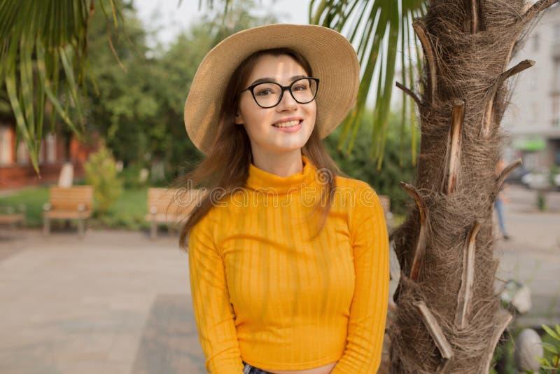 Bella giovane donna alla moda che sorride nel parco, cima gialla, jeans, scarpe da tennis, cappello immagine stock libera da diritti