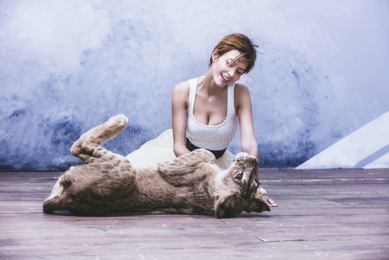Bella giovane donna alla moda con un piccolo cucciolo di leone vivo immagine stock libera da diritti