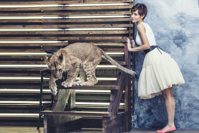 Bella giovane donna alla moda con un piccolo cucciolo di leone vivo fotografia stock