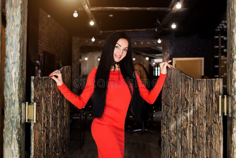 Bella giovane donna alla moda con un sorriso che esamina la macchina fotografica nella cabina Modo, gioventù, salute, cura immagini stock