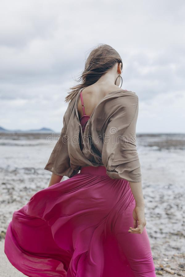 Bella giovane donna alla moda in gonna rossa che cammina sulla spiaggia immagine stock libera da diritti