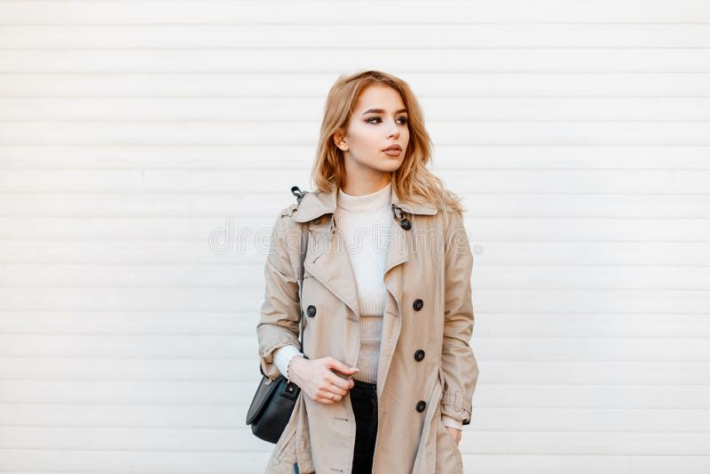 Bella giovane donna alla moda in un cappotto alla moda della molla in una maglietta bianca con i supporti neri d'avanguardia di u immagine stock