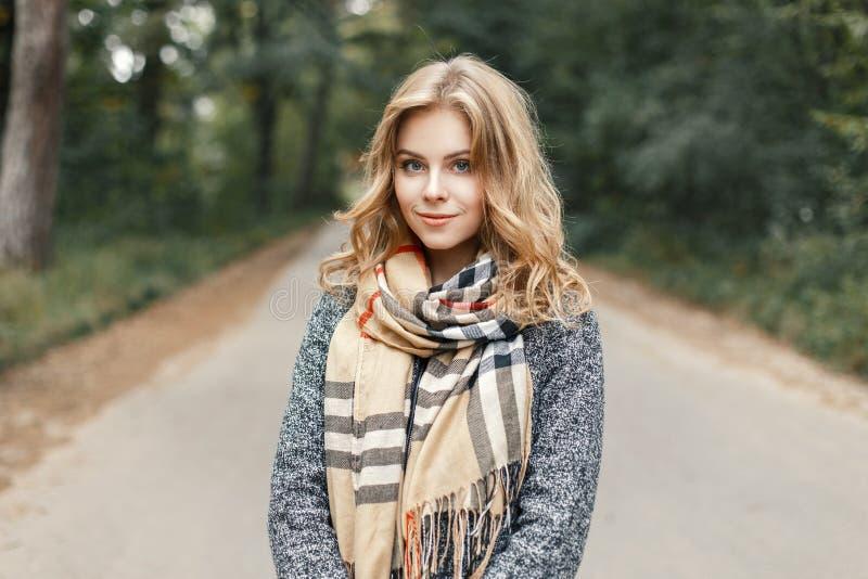 Bella giovane donna alla moda in una camminata calda del cappotto e della sciarpa fotografia stock libera da diritti