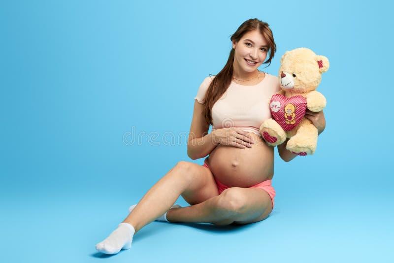 Bella giovane donna allegra felice con l'orsacchiotto che si siede sul pavimento immagine stock libera da diritti