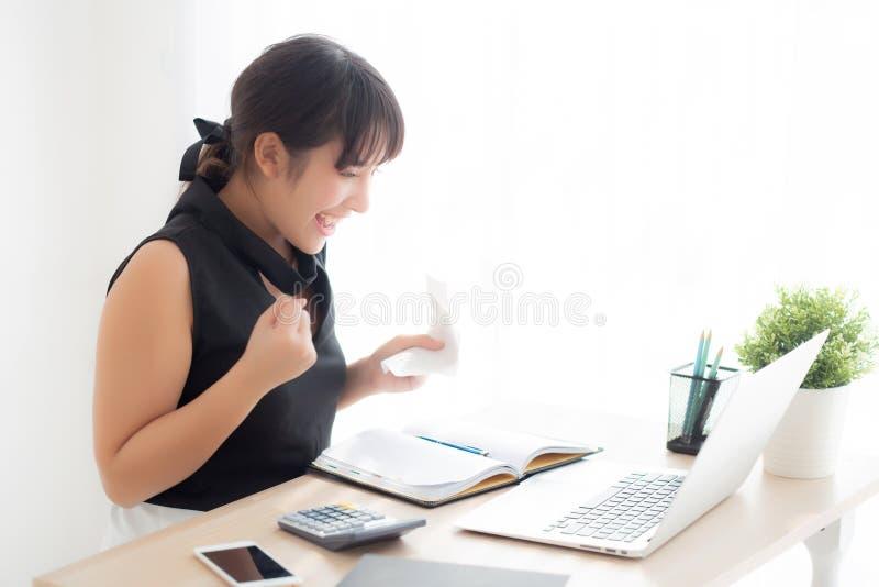 Bella giovane donna asiatica che calcola la famiglia di finanza e che scrive taccuino sullo scrittorio fotografie stock libere da diritti
