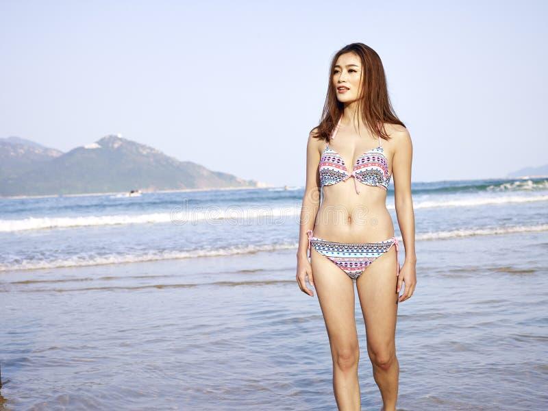Bella giovane donna asiatica che cammina sulla spiaggia immagine stock libera da diritti