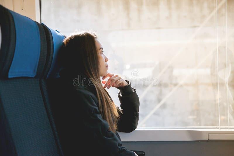 Bella giovane donna asiatica che si siede sul treno espresso a Tokyo, Giappone immagini stock