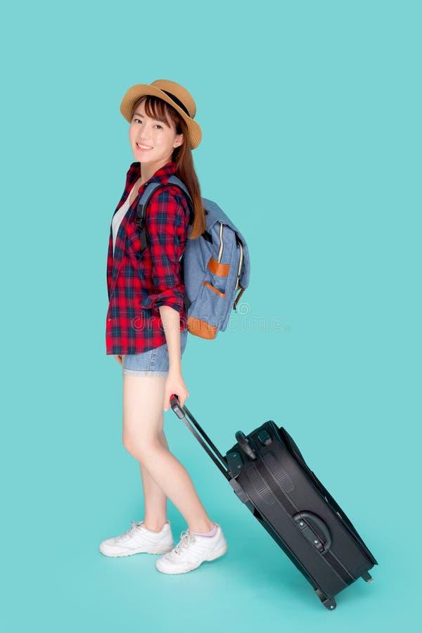 Bella giovane donna asiatica che tira valigia isolata su fondo blu, ragazza dell'Asia che ha espressivo immagini stock libere da diritti