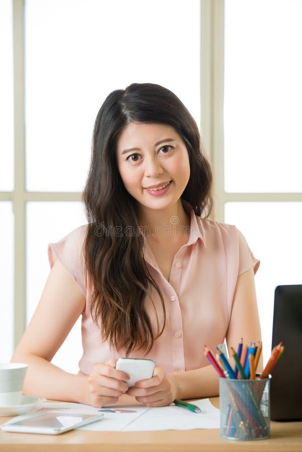 Bella giovane donna asiatica che usando invio di messaggi di testo dello Smart Phone fotografia stock
