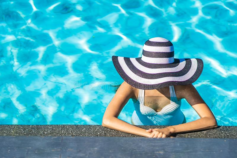 Bella giovane donna asiatica con il cappello nella piscina per il viaggio e la vacanza immagini stock libere da diritti