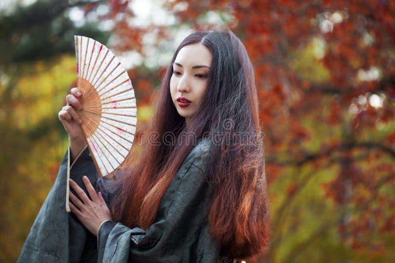 Bella giovane donna asiatica con il fan su fondo dell'acero rosso fotografie stock libere da diritti