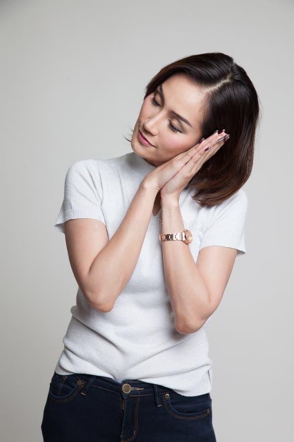 Bella giovane donna asiatica con il gesto di sonno fotografia stock libera da diritti