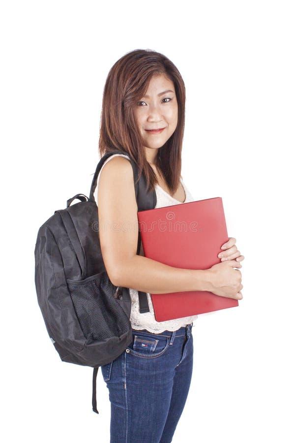 Bella giovane donna asiatica con lo zaino che tiene libro rosso fotografia stock libera da diritti