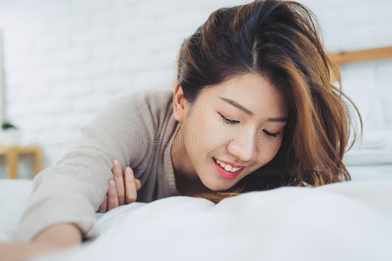 Bella giovane donna asiatica del ritratto sul letto a casa di mattina fotografia stock libera da diritti
