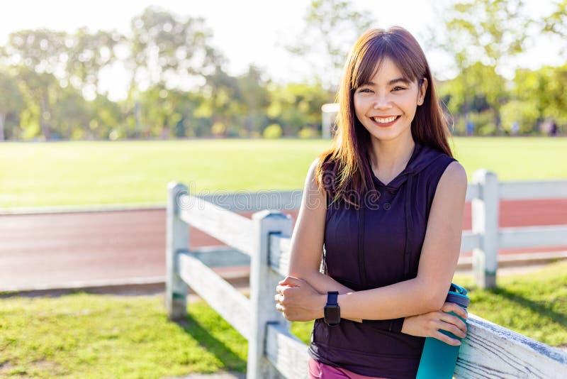Bella giovane donna asiatica felice che sorride alla macchina fotografica, stante e tenente la sua bottiglia di acqua ad un campo immagini stock libere da diritti