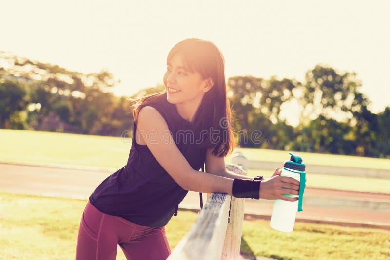 Bella giovane donna asiatica felice che sorride e che sta tenente il suo bottole dell'acqua ad un campo all'aperto su una mattina immagine stock