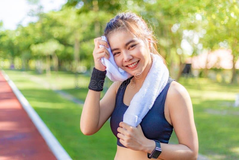Bella giovane donna asiatica felice che usando il suo asciugamano bianco per pulire del suo sudore dopo il suoi funzionamento ed  fotografia stock libera da diritti