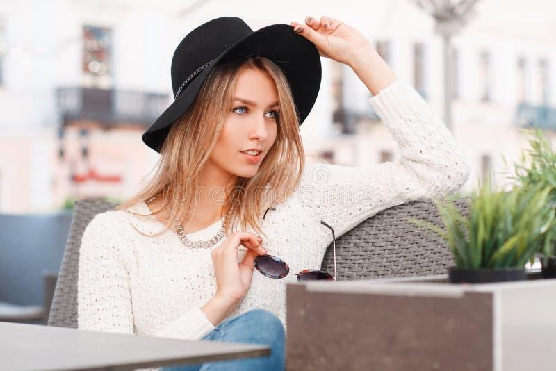 Bella giovane donna attraente in un maglione bianco tricottato in jeans in un cappello elegante alla moda che si siede su un sofà fotografia stock libera da diritti