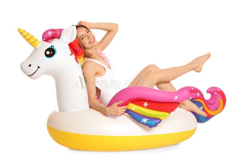 Bella giovane donna in bikini alla moda con l'anello gonfiabile dell'unicorno su bianco immagini stock libere da diritti