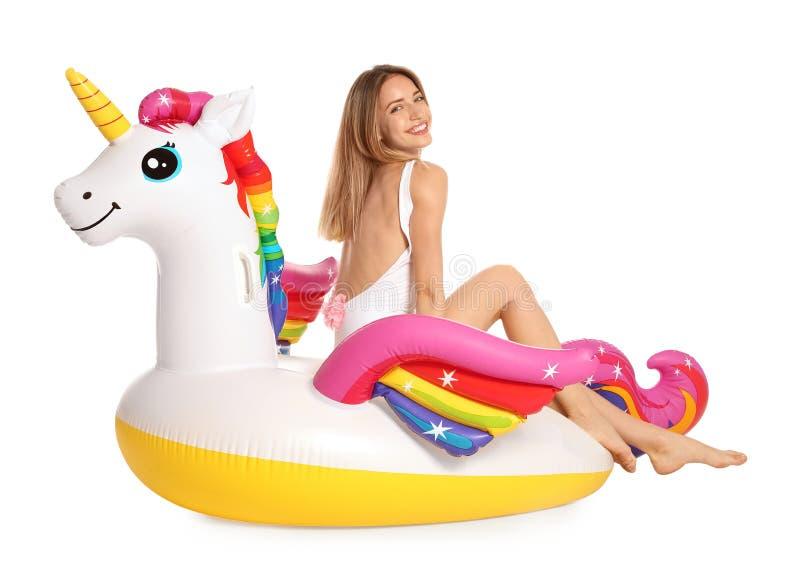 Bella giovane donna in bikini alla moda con l'anello gonfiabile dell'unicorno su bianco fotografie stock