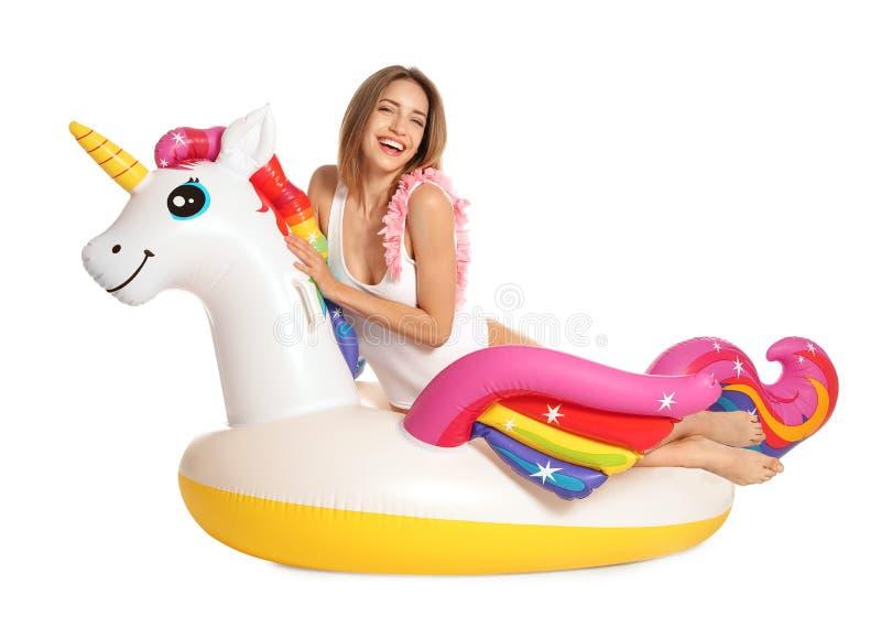 Bella giovane donna in bikini alla moda con l'anello gonfiabile dell'unicorno su bianco fotografia stock