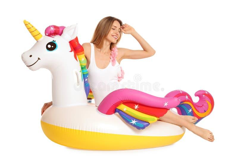 Bella giovane donna in bikini alla moda con l'anello gonfiabile dell'unicorno fotografie stock libere da diritti