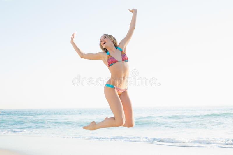 Bella giovane donna bionda che salta sulla spiaggia fotografia stock libera da diritti