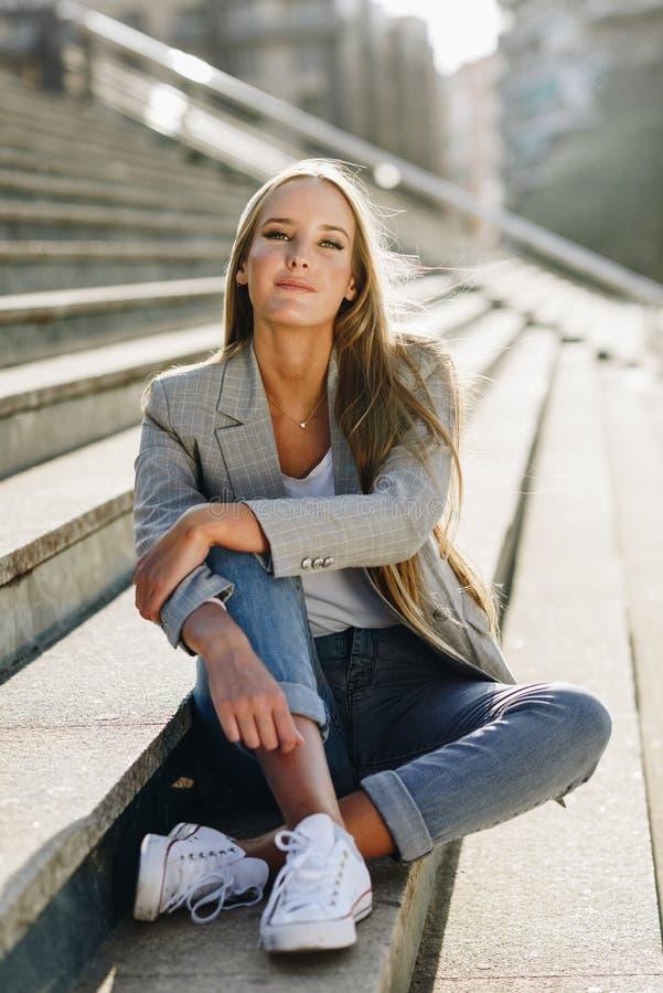 Bella giovane donna bionda che si siede sui punti urbani fotografie stock libere da diritti