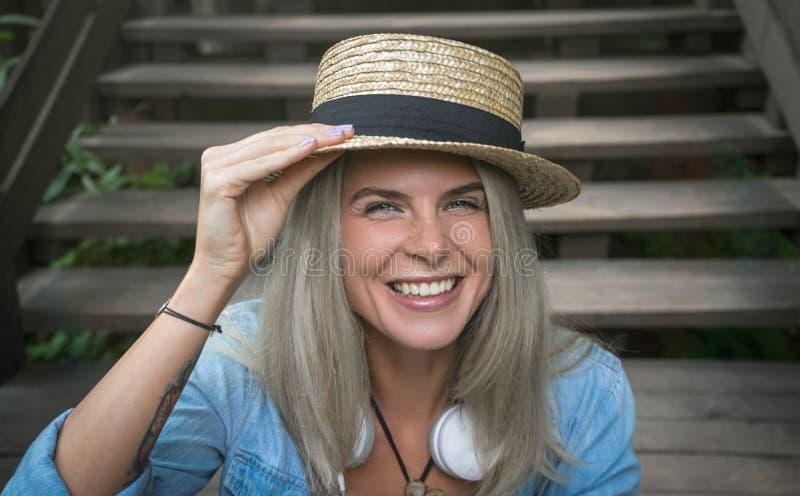 Bella giovane donna bionda dei pantaloni a vita bassa in un cappello di paglia che si siede sui punti di legno nel parco che sorr fotografia stock libera da diritti