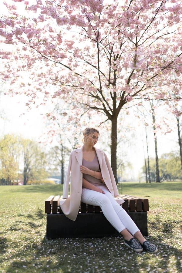 Bella giovane donna bionda nel parco di Sakura Cherry Blossom in primavera che gode della natura e del tempo libero durante lei c fotografie stock libere da diritti