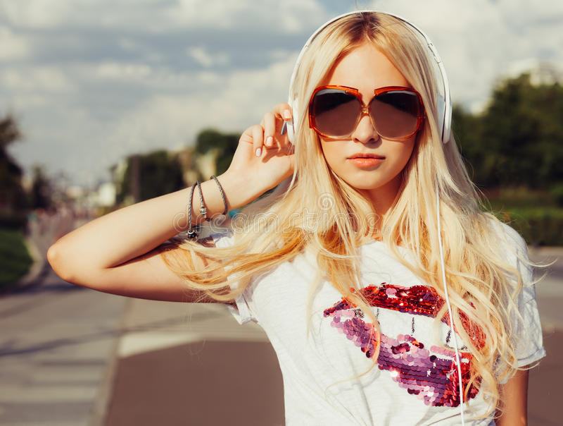 Bella giovane donna bionda in occhiali da sole d'annata che ascolta la musica con le cuffie Ritratto del primo piano immagine stock