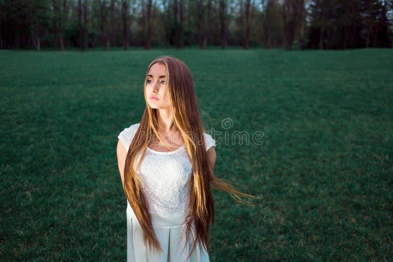 Bella giovane donna bionda sola in un parco mistico di sera immagine stock libera da diritti