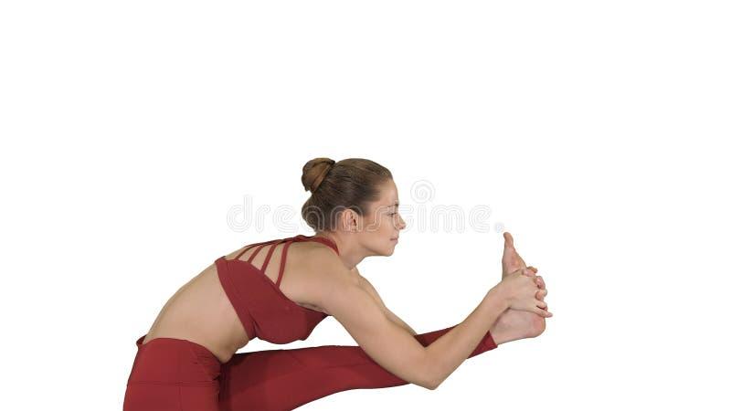 Bella giovane donna bionda sportiva in abiti sportivi che fanno Utthita Hasta Padangushthasana su fondo bianco fotografia stock