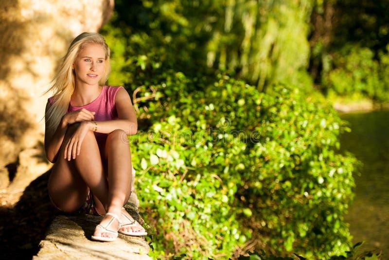 Bella giovane donna bionda su un arownd della passeggiata la città vicino al castello nel giorno soleggiato di estate fotografia stock
