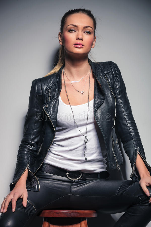 Bella giovane donna bionda in vestiti di cuoio che si siedono sulle feci fotografia stock libera da diritti