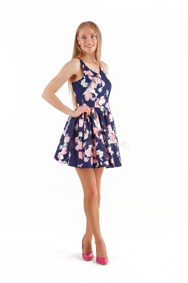 Bella giovane donna bionda in vestito blu con ricamo floreale isolato su fondo bianco fotografia stock
