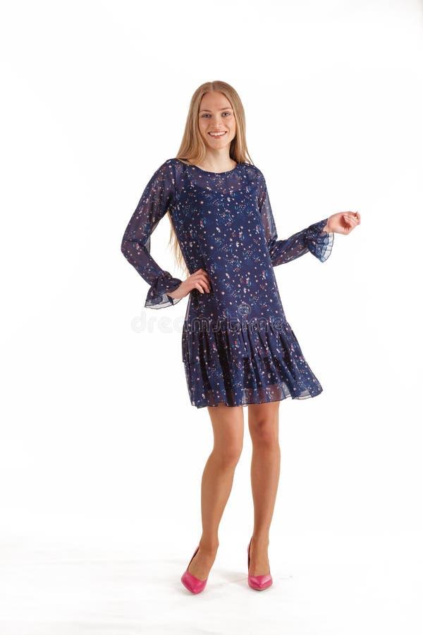 Bella giovane donna bionda in vestito blu scuro con la stampa floreale isolata su fondo bianco immagine stock libera da diritti