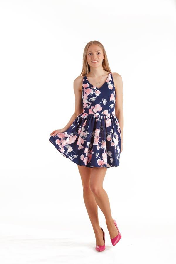 Bella giovane donna bionda in vestito blu scuro con la stampa floreale isolata su fondo bianco fotografia stock libera da diritti