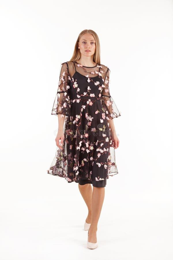 Bella giovane donna bionda in vestito nero con ricamo floreale isolato su fondo bianco fotografie stock