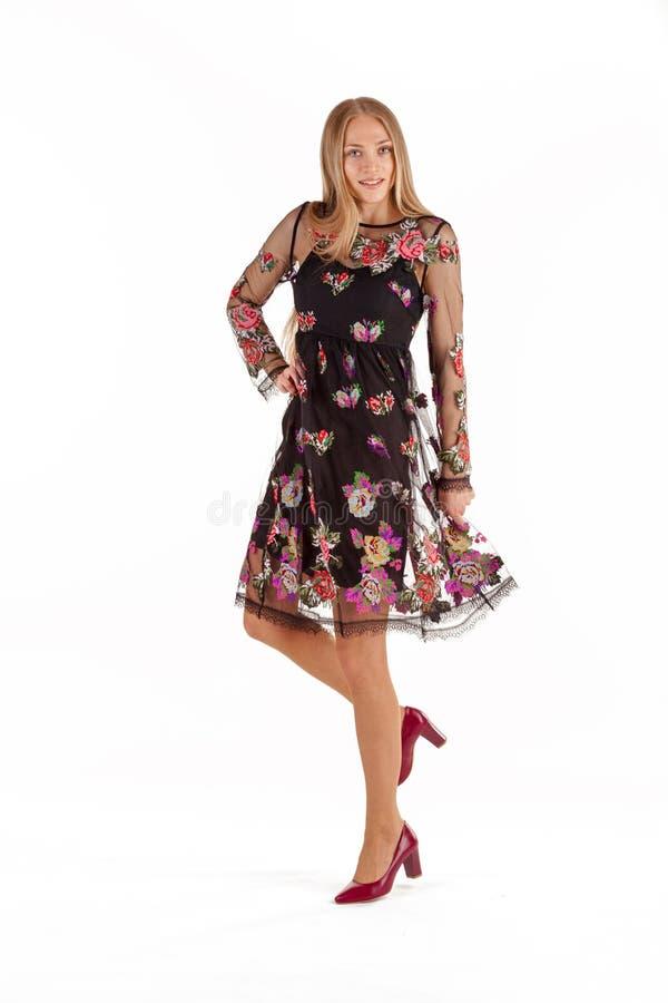 Bella giovane donna bionda in vestito nero con ricamo floreale isolato su fondo bianco fotografia stock libera da diritti