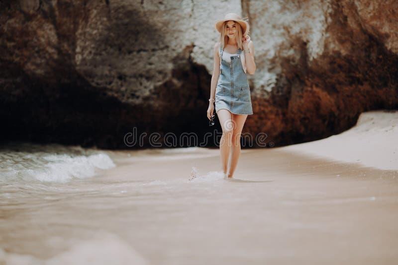 Bella giovane donna in cappello ed occhiali da sole che cammina sulla linea costiera al giorno soleggiato di estate fotografie stock