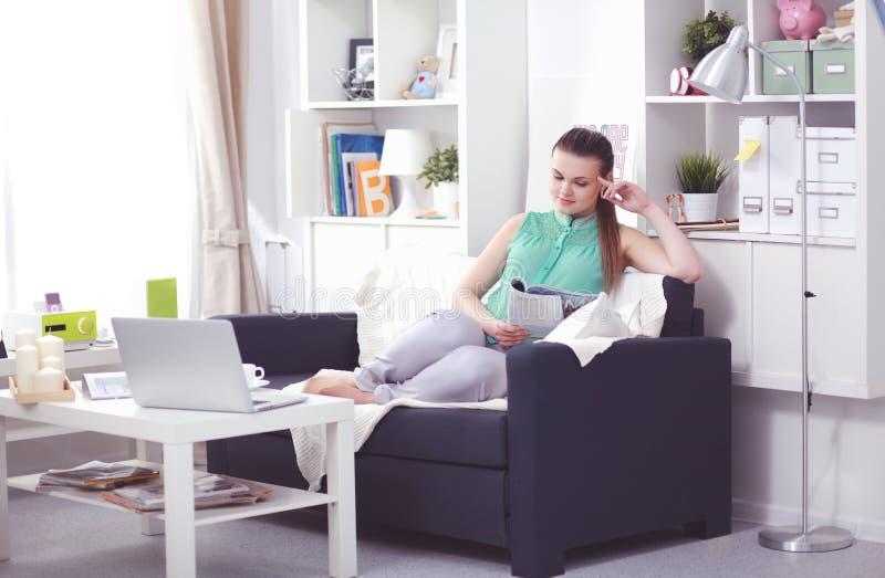 Bella giovane donna castana a casa che si siede sul sof? o sul divano facendo uso del suo computer portatile immagini stock