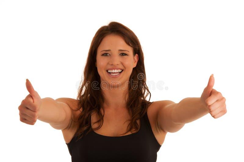 Bella giovane donna castana che gesturing successo con il pollice su io immagine stock libera da diritti